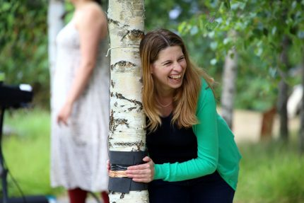 A woman smiles broadly as she hugs a tree and it makes a sound.