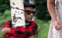 A man wearing sunglasses and a checked shirt hugs a tree tightly.