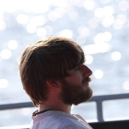 Ben is photographed in profile, in repose against a sparkling sea