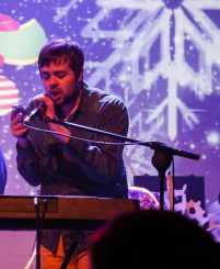 Louis performs onstage with keyboard & microphone and bold visuals