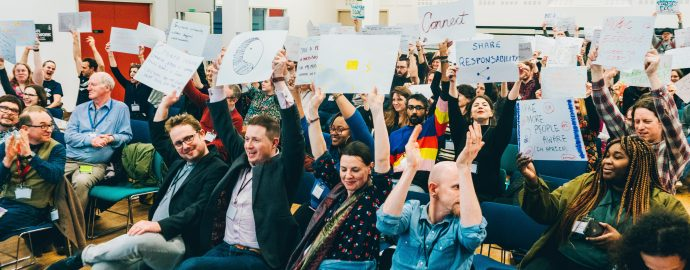 Conference attendees wave placards with pledges for change written on them
