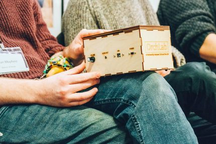 Close up of hands holding a plywood box with switches on it