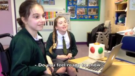 Two girls in school are talking to someone off camera, with a Skoog box in front of them