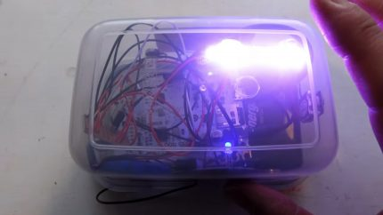 A tupperware box full of wires shines with a bright light in one corner