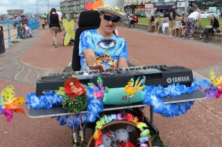 Steve is pictured in his wheelchair on the seafront. It is adapted with a large keyboard and bass drum and is decorated with colourful flowers