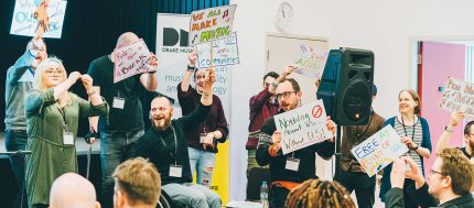 The Drake Music team are staging a protest with colourful signs onstage at a conference