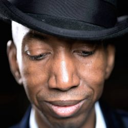 Dike wears a black trilby hat and his black suit and white shirt are just visible. He looks down with the brim of his hat pulled low and a slight smile