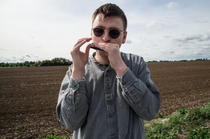 Oliver stands on the Fens before a ploughed field. He is wearing round shades and looking into the camera as he plays his harmonica