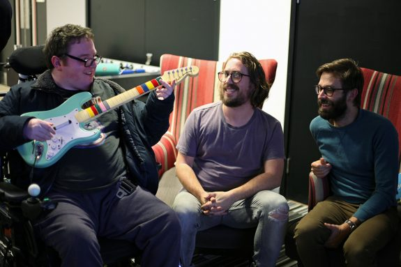 Sam, Billy and Andy at DMLab. Sam is holding a reimagined version of a Guitar Hero guitar which now is an actual instrument