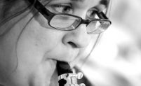 Sonia is pictured in black and white close up, playing a wind instrument