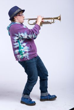 Robyn is shown in profile playing a trumpet, leaning back, knees bent, wearing a purple hoodie, jeans and trilby hat