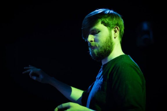 Ben stands conducting, his arms outstretched against a dark backdrop as he is lit from one side with a green light.
