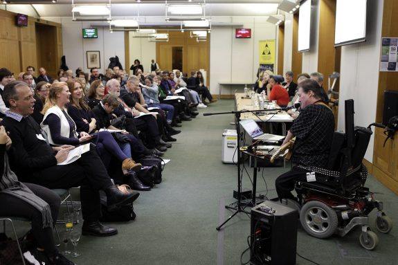 John is playing music to an audience in a large meeting room, rows of people smile as they listen