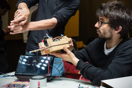 A maker holds up a piece of kit he is building as he looks at another maker miming a shape with his hands
