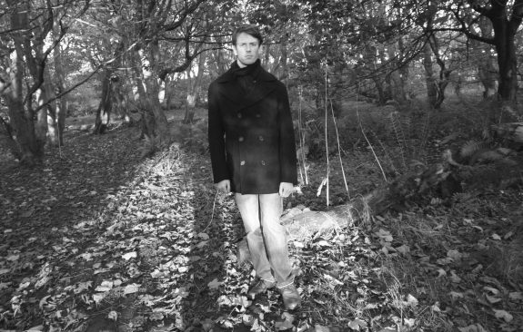 Ewan is pictured in black and white in an autumnal woodland scene, wrapped up warm in a double-breasted coat