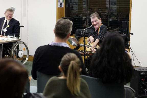 John gives a sideways grin to the crowd as he plays protest songs in Portcullis House