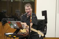 John is playing music, sitting in his wheelchair in front of a laptop and tech set up, his adapted guitar the kellycaster slung round his neck with a rainbow strap