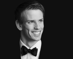 A formal portrait of Ewan who smiles as he looks off-camera. He is wearing a tuxedo and bowtie and his hair is neatly combed to one side.
