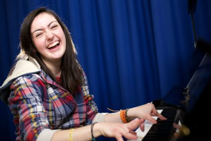 Sarah sits at the piano with a big smile, she has long brown hair and wears a plaid shirt.