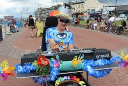 Steve poses with his synth and keyboard wearing a brightly coloured shirt and a hat with flowers on