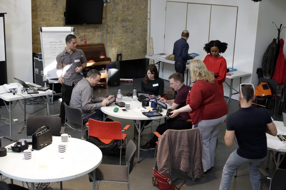 Six people are getting involved with making music using technology. They loosely gathered around a table, but are each doing something different