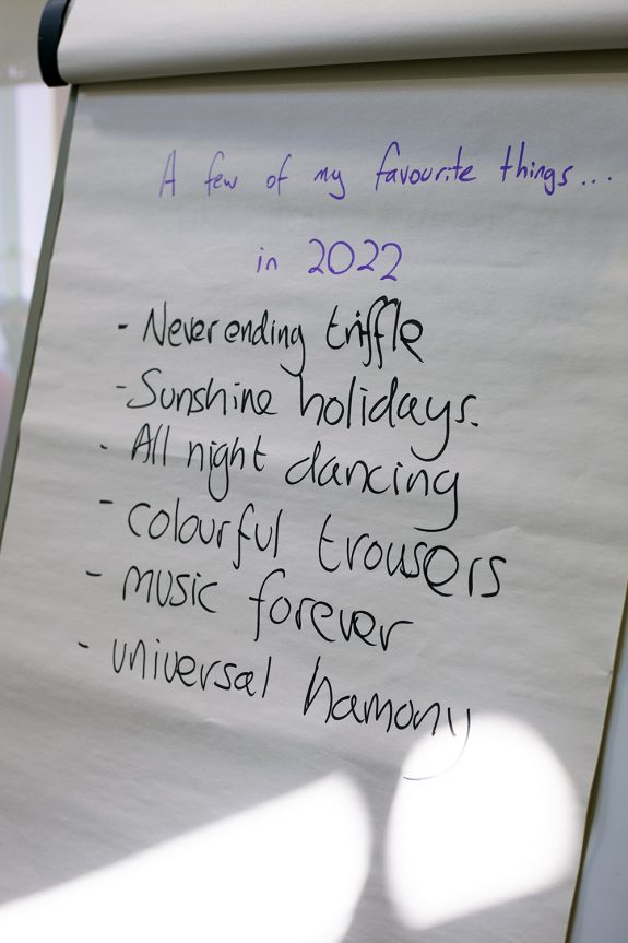 A close up of a flip chart page with a list of 'favourite things in 2022': never ending trifle, sunshine holidays, all night dancing, colourful trousers, music forever, universal harmony