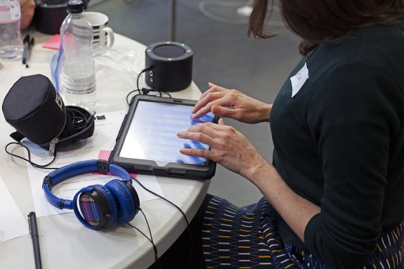 Hands poised lightly above an iPad in a sturdy case. Chunky headphones lie on the table next to it.