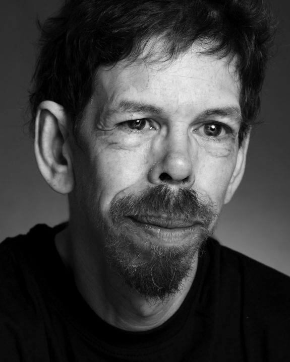Jez Colborne is an older white man with short hair, expressive features and a short beard.