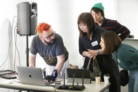 Kris and a group of women work at a laptop. He is wearing MuMiGloves