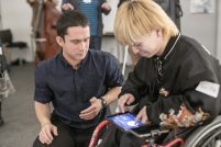 Ben works with a musician in a wheelchair who is playing an iPad