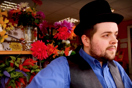 Wearing a jaunty top hat, waistcoat and blue shirt, Louis stands in a shop window pretending to be a mannequin.