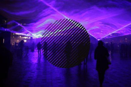 A mysterious image of blues and purples, laser lights create shapes in smoke and people are seen walking in silhouette