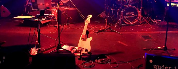 A shortened guitar sits on a stage lit in red and blue