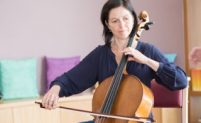Georgina is a white woman with brown, chin length hair, playing a cello.