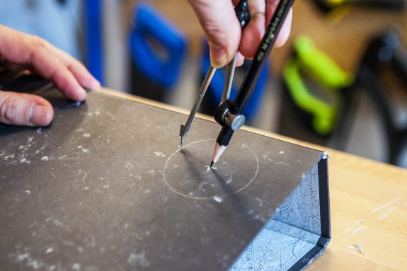 A compass is being used to draw and score a circle on the front of a lever arch folder