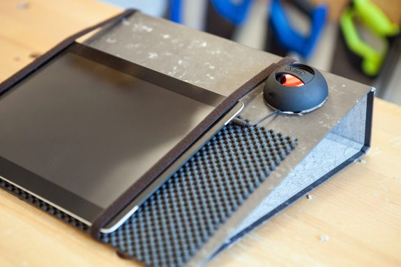 A lever arch file has an iPad strapped to it and a portable speaker set into the front of the file