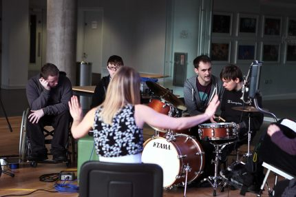 A music leader holds out both arms with her palms up as she tells the group of young musicians to stop playing