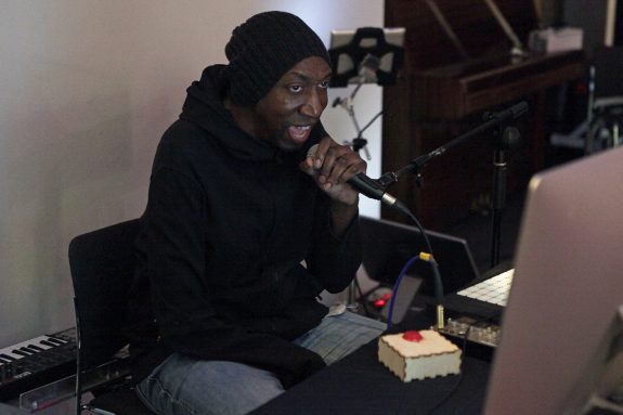 Dike sings into a microphone, he is a black man wearing a slouchy beany hat