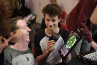 Two men are playing music with an iPad and smiling