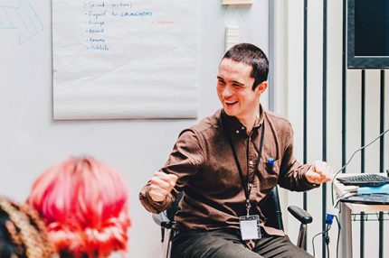 A young man with short brown hair smiles broadly as he leads a workshop on music technology