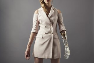 A woman wearing a fashionable trench coat with short sleeves holds out both arms, one is prosthetic from the elbow down and made of a see through material.