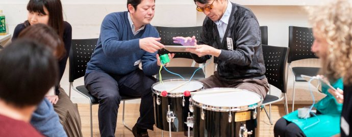 A music teacher supports a learner to use an iPad as an instrument