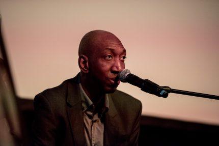 Dike sings into a microphone wearing a dark blazer