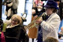 Robyn wears a trilby and plays trumpet for an enthusiastic listener
