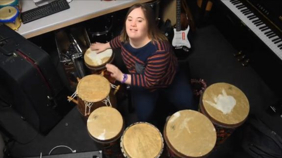 A young woman plays a set of hand percussions