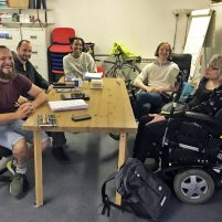 The group smiles, gathered a table in a meeting room.