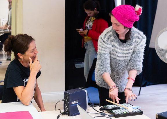 Two women smile as they trigger sounds with music technology