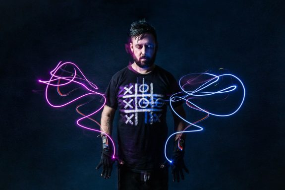 Kris stands, his eyes closed and hands with gloves on by his sides. Around his lighting shows the paths of his hands movement, like traced wings.