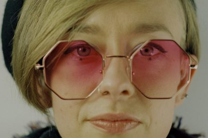 Sally looks directly at the camera, her lips pressed together, not smiling. She has a sweeping blond fringe and hexagonal pink tinted glasses.