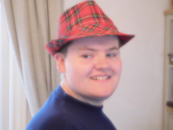 Robbie smiles and looks off to one side, he has a smoothly shaven face and wears a red tartan trilby.